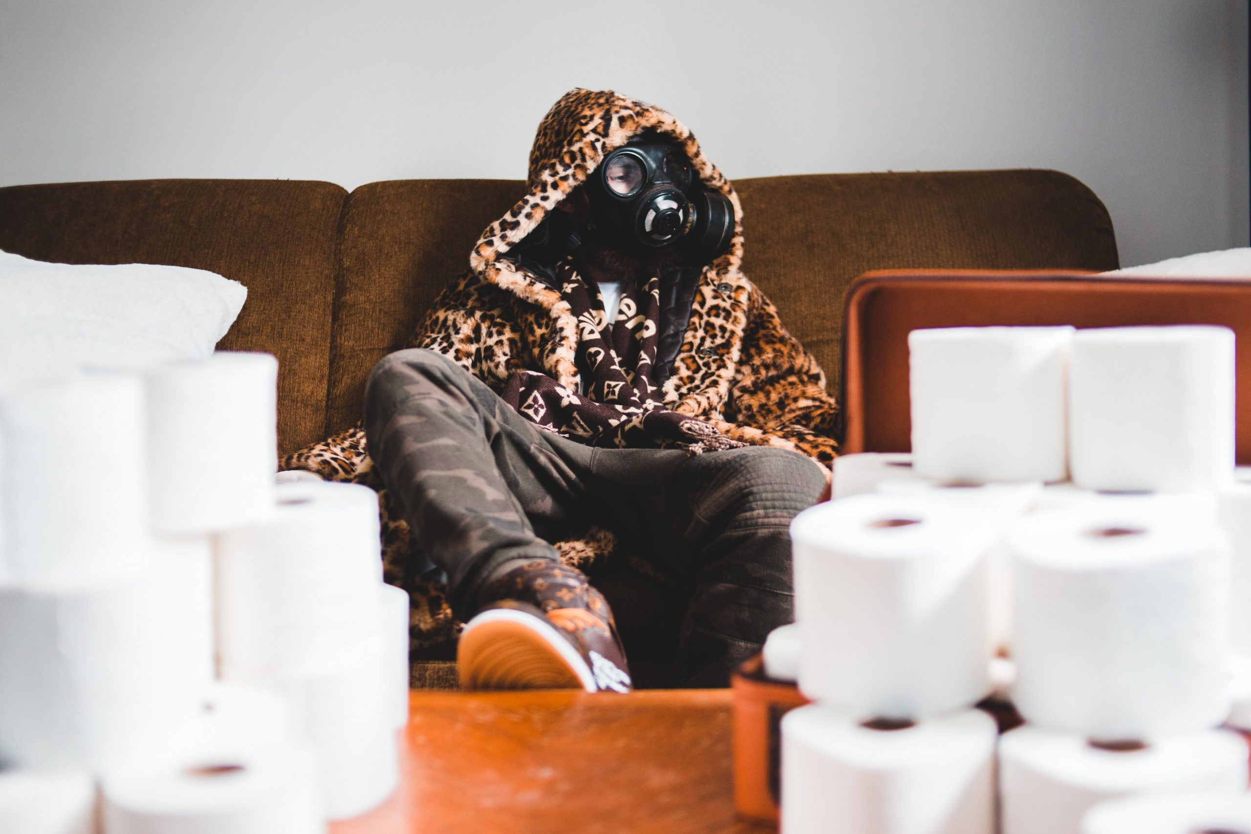 A person wearing a fashionable coat wearing a respiratory mask sitting behind a pile of toilet paper.