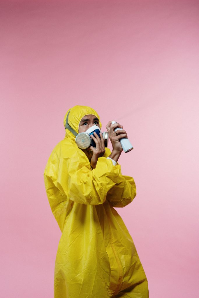 person-in-yellow-coveralls-holding-spray-bottle